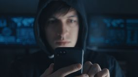El pirata informático peligroso en la capilla utiliza un smartphone en un centro de datos secreto llenado de las pantallas metrajes