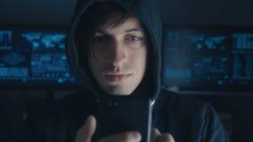 El pirata informático peligroso en la capilla utiliza un smartphone en un centro de datos secreto llenado de las pantallas almacen de video
