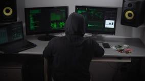 El pirata informático piensa en cómo el suyo programa del corte y después da vuelta precipitadamente a la pantalla de monitor y c almacen de video