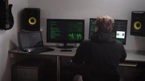 El pirata informático recoge los diversos datos del ordenador para cortar la base de datos Hombre joven especialmente entrenado q metrajes