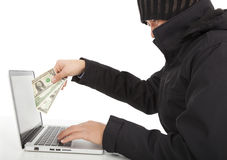 El pirata informático roba el dinero de Internet con el ordenador portátil fotos de archivo