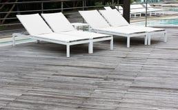 El piso de madera, la piscina y la piscina blanca acuestan Foto de archivo libre de regalías