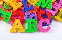 El plástico coloreó las letras ABC del alfabeto en un blanco Foto de archivo libre de regalías
