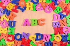 El plástico coloreó las letras ABC en un fondo de madera Fotos de archivo libres de regalías