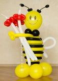 El plástico colorido manosea la abeja con las flores rojas fotos de archivo