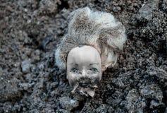 El plástico escalda la cabeza de la muñeca que miente en una pila de suciedad Foto de archivo