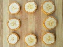 El plátano corta el marco en fondo de madera Fotos de archivo
