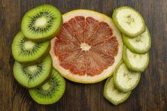 El plátano del pomelo del kiwi arregló maravillosamente las vitaminas jugosas frescas tropicales en la madera Imagen de archivo