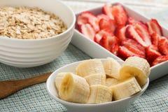 El plátano, fresas, avena forma escamas en cuenco Imagen de archivo