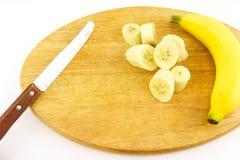 El plátano pelado cortado, cuchillo y madera el tajar Fotografía de archivo libre de regalías