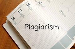 El plagio escribe en el cuaderno Foto de archivo