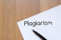 El plagio escribe en el cuaderno Fotos de archivo
