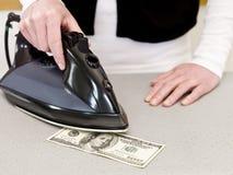 El planchar del dinero Foto de archivo libre de regalías