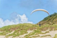 El planeador de caída se eleva bajo sobre las dunas herbosas Imagen de archivo