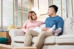 El planeamiento asiático de los pares para adornar la casa después de mover al nuevo hogar, sentándose en el sofá con relaja la e fotos de archivo libres de regalías