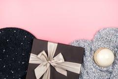 El plano acogedor pone con ropa, la caja de regalo y una vela fotos de archivo