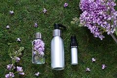 El plano cosmético de la botella pone con las flores de la lila Composición de la visión superior imagen de archivo