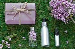 El plano cosmético de la botella pone con las flores de la lila Composición de la visión superior fotografía de archivo