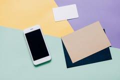 El plano creativo pone el escritorio del espacio de trabajo del estilo con smartphone Fotografía de archivo