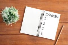 El plano creativo pone la foto del escritorio del espacio de trabajo con el cuaderno 2018 de la lista del Año Nuevo de la meta y  Fotos de archivo