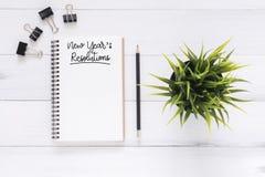 El plano creativo pone la foto del escritorio del espacio de trabajo con el cuaderno de la lista de la resolución del Año Nuevo y Imagen de archivo libre de regalías