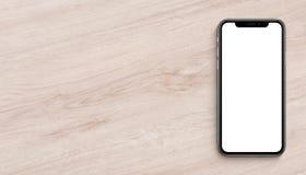 El plano de la maqueta de Smartphone pone la visión superior que miente en bandera de madera del escritorio de oficina con el esp foto de archivo