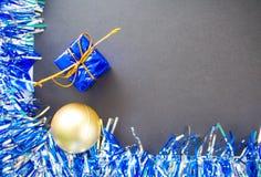 El plano de la Navidad o del Año Nuevo enmarcó el lugar del texto Guirnalda chispeante azul de la cinta Bola y regalo del oro Fotos de archivo