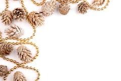 El plano de la Navidad pone la mesa de la maqueta, conos del pino y gotas del oro en un fondo blanco Foto de archivo libre de regalías