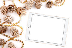 El plano de la Navidad pone la mesa de la maqueta, conos del pino y la tableta en un fondo blanco Imagen de archivo libre de regalías
