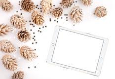 El plano de la Navidad pone la mesa de la maqueta, conos del pino y la tableta en un fondo blanco Fotografía de archivo