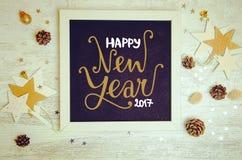 El plano de las decoraciones y de los objetos del Año Nuevo pone la foto con el marco negro de la pizarra Fotos de archivo libres de regalías