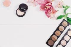 El plano decorativo pone la composición con los productos de maquillaje, los cosméticos y las flores Endecha plana, opinión super Imagen de archivo libre de regalías