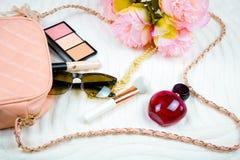 El plano femenino pone con las gafas de sol y el parfume del bolso Fondo blanco foto de archivo libre de regalías