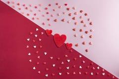 El plano hermoso pone el modelo de corazones con tres corazones rojos Foto de archivo