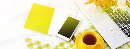 El plano largo de la bandera pone el teléfono, la taza amarilla de té, el ordenador portátil y las flores en la manta blanca con  Fotos de archivo libres de regalías