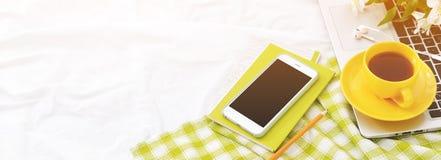 El plano largo de la bandera pone el teléfono, la taza amarilla de té, el ordenador portátil y las flores en la manta blanca con  Imagen de archivo