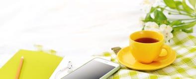 El plano largo pone el teléfono de la bandera, la taza amarilla de té y las flores en la manta blanca con la servilleta verde Fotografía de archivo libre de regalías
