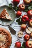 el plano pone con la empanada de manzana, el servidor de la torta, las manzanas frescas y las hojas verdes foto de archivo