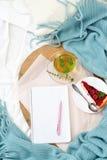 El plano vertical pone el desayuno en cama con el pastel de queso de la frambuesa, té de la menta y abre el cuaderno Imágenes de archivo libres de regalías