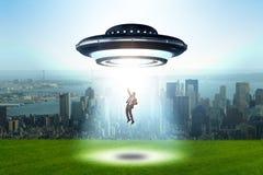 El platillo volante que secuestra al hombre de negocios joven foto de archivo libre de regalías