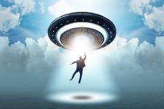 El platillo volante que secuestra al hombre de negocios joven imagen de archivo