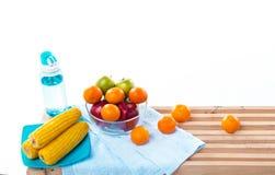 El plato amarillo del maíz puso al lado de la botella de agua y el cuenco de fruta, la manzana roja de la manzana, anaranjada y v foto de archivo
