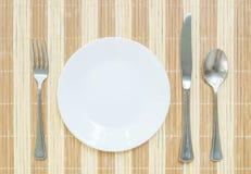 El plato de cerámica blanco del primer con la bifurcación y cuchara y cuchillo inoxidables en la estera de madera texturizó el fo Fotografía de archivo libre de regalías