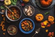 El plato del guisado de la calabaza del vegano con espinaca sirvió en cuenco con la cuchara en fondo oscuro de tabla de cocina co imagenes de archivo