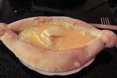 El plato georgiano tradicional es el khachapuri de Adjara: pasta en la forma de un barco, queso del suluguni, un huevo fotografía de archivo libre de regalías