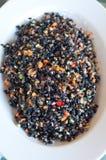 El plato negro del arroz sazonó con los tomates, zanahorias, aceite de oliva y Imagenes de archivo