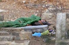 El pobre hombre sin hogar duerme en un cementerio Foto de archivo libre de regalías