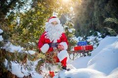 El poco llevar de Papá Noel regalos a través de un bosque del invierno Imagen de archivo