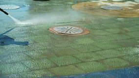 El poder del trabajador lava el encintado cerca de la acera en centro de la ciudad Calles de limpieza de la ciudad con la manguer metrajes