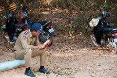 El policía camboyano lee en Angkor Imagenes de archivo